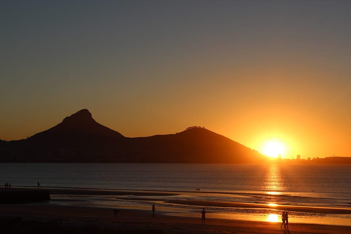 Fernreisen mit Kindern wohin? Beliebte Urlaubsziele für Familien – Südafrika, Sonnenuntergang am Strand von Milnerton